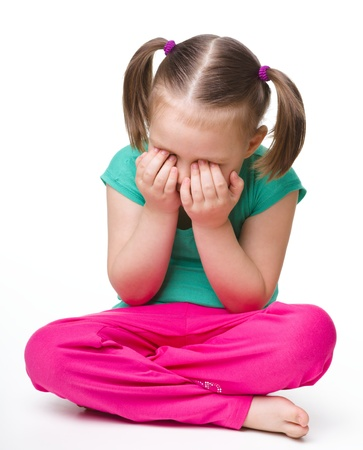 Little girl is sitting on floor and crying, isolated over white Stock Photo - 9395801