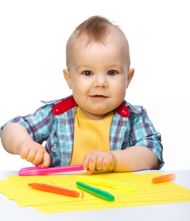 Happy little boy is playing with colorful markers, isolated over white photo
