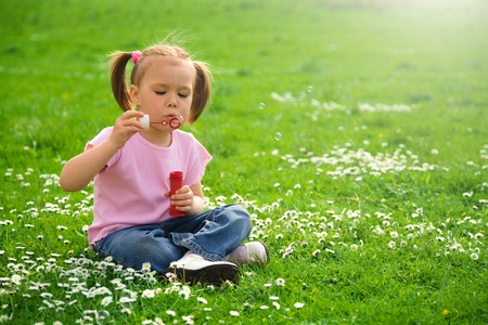 Little girl is sitting on green meadow and blows a soap bubbles photo