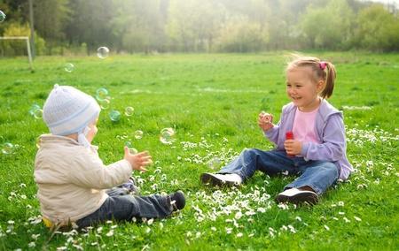 ni�os jugando parque: Dos ni�os est�n sentados en el prado verde y soplan las pompas de jab�n