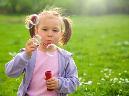 Little girl blows soap bubbles on green meadow photo