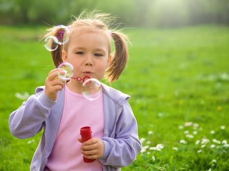 Little girl blows soap bubbles on green meadow photo