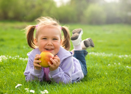 Little girl is laying on green meadow and going to eat a red apple photo