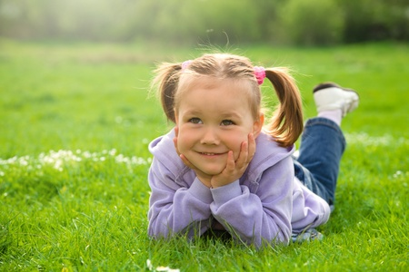 Little girl is laying on green meadow holding her head with hands photo