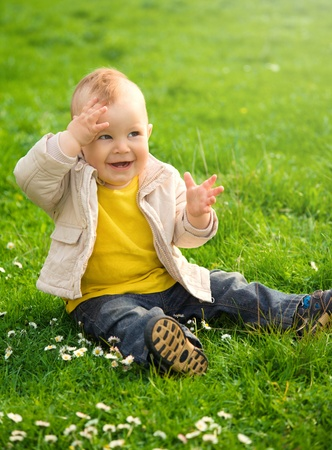 Little boy is sitting on green meadow covering his eyes from the sun photo