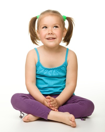 little girl sitting: Portrait of a cute little girl sitting on floor, isolated over white