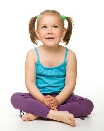 ni�os pensando: Retrato de una linda ni�a sentada en el suelo, aislada en blanco Foto de archivo