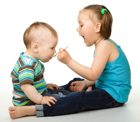 playing with spoon: Sister is feeding her little brother using spoon, isolated over white