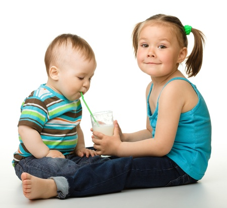 Sister is feeding her little brother and he drinks milk using drinking straw, isolated over white photo