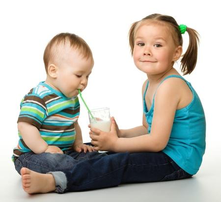 drinking straw: Sorella sta alimentando il suo fratellino e bevande di lui usando latte cannuccia, isolato over white
