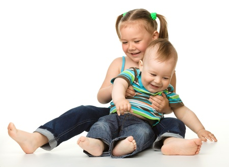 sister and brother: Two children (a girl and a boy) is having fun while sitting on floor, isolated over white