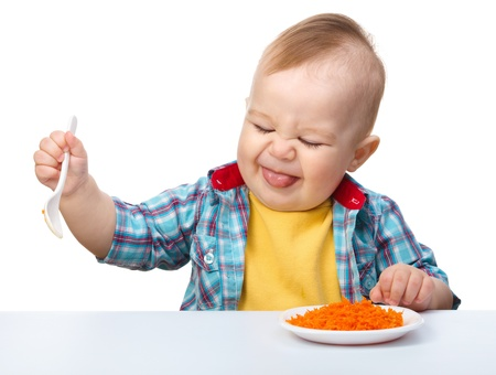 Little boy refuses to eat making unpleasant grimace, isolated over white photo