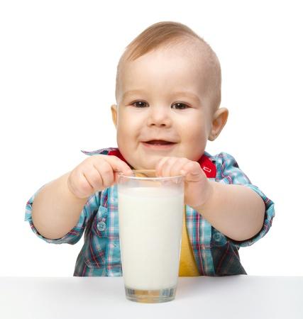vaso de leche: Ni�o lindo mantiene gran vaso de leche mientras estaba sentado a la mesa, aislada en blanco