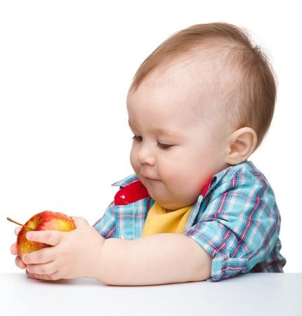 Ni�o lindo es comer manzana roja mientras estaba sentado a la mesa, aislada en blanco Foto de archivo - 9557611