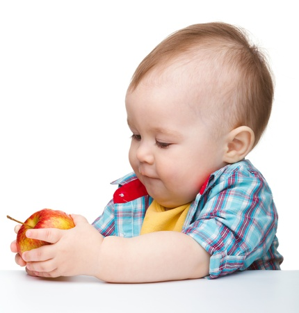 Niño lindo es comer manzana roja mientras estaba sentado a la mesa, aislada en blanco Foto de archivo - 9557611