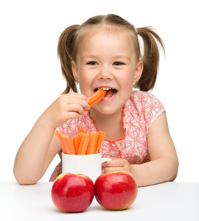 kids eat: Cute little girl eats carrot and apples, isolated over white