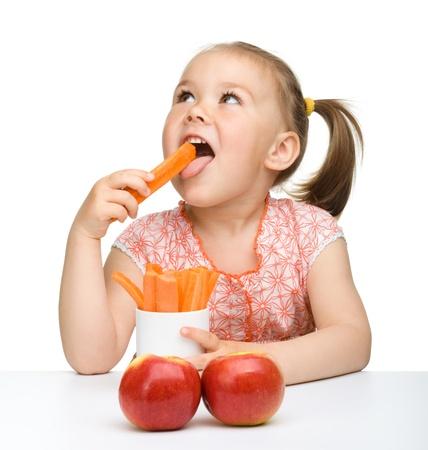 merenda: Cute little girl si nutre di carota e mele, isolate over white Archivio Fotografico