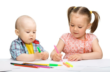 Two children, girl and boy, are drawing on paper using markers, isolated over white photo