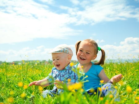 Two children (a girl and a boy) are having fun on green meadow photo