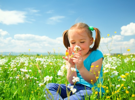 flowers horizontal: Little girl is smelling flowers while sitting on green meadow