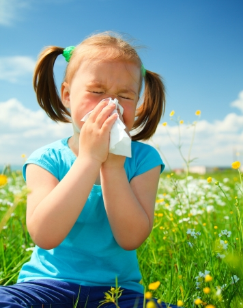 allergic: Little girl is blowing her nose while sitting on green meadow