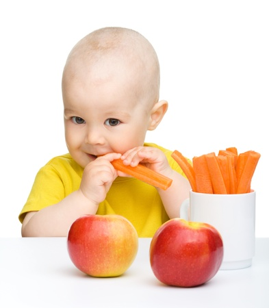 kid eat: Cute little boy eats carrot and apples, isolated over white Stock Photo