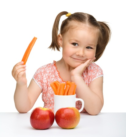 Cute little girl eats carrot and apples, isolated over white Stock Photo - 9609749