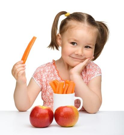 Schattig klein meisje eet wortel en appels, geïsoleerd over Wit