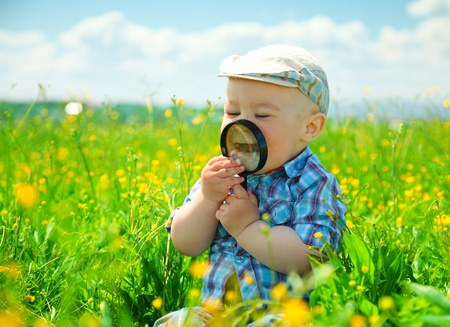 Little boy is playing with magnifying glass on green meadow photo
