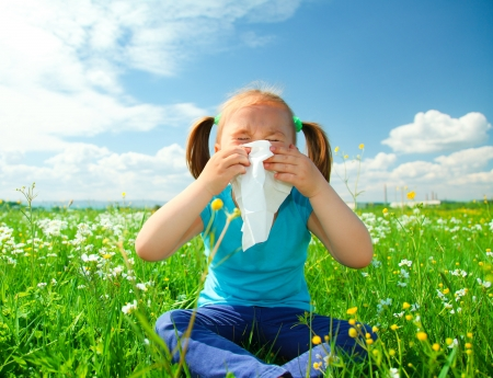 Little girl is blowing her nose while sitting on green meadow photo