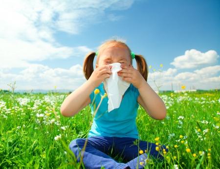 estornudo: Ni�a sopla la nariz mientras estaba sentado en el prado verde Foto de archivo