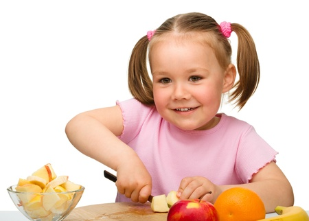 Little girl is cutting fruits for salad using kitchen knife, isolated over white photo
