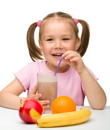 Cute little girl drinks fruit juice using drinking straw, isolated over white photo