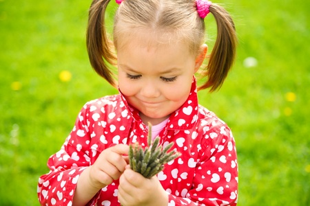 Cute little girl holding bunch of herbs, shallow depth of field photo