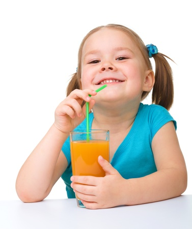 Cute little girl drinks orange juice using drinking straw, isolated over white