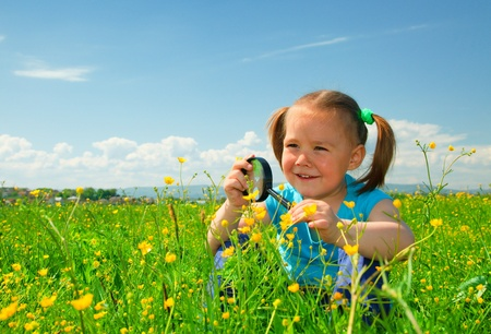 Little girl is playing on green meadow and examining field flowers using magnifying glass photo