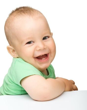 nourrisson: Portrait d'un adorable petit gar�on gai, qui sourit alors qu'il �tait assis � table, isol� sur blanc Banque d'images
