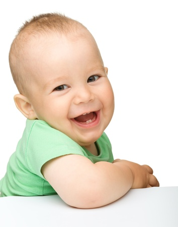infants: Portrait of a cute cheerful little boy, who is smiling while sitting at table, isolated over white