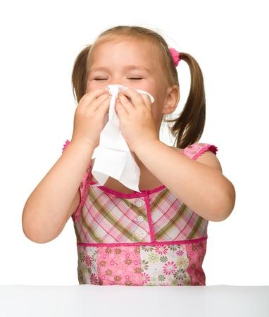 ni�os enfermos: Ni�a sopla su nariz, aislado en blanco Foto de archivo