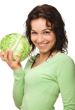 Beautiful young girl with green cabbage, isolated over white photo