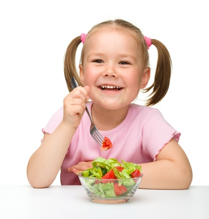Cute little girl eats vegetable salad using fork, isolated over white photo