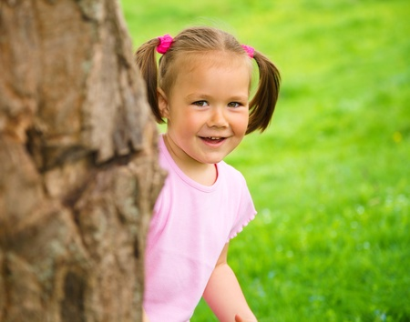 Cute little girl is playing hide and seek outdoors photo