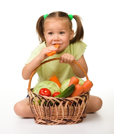 Cute little girl eats carrot while sitting on the floor with basket full of vegetables, isolated over white Stock Photo - 9950645