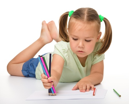crayon drawing: Cute little girl is drawing while laying on the floor, isolated over white