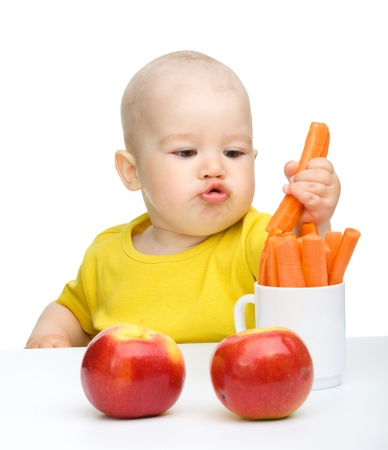 kid eat: Little boy pulling up carrot from a cup, isolated over white