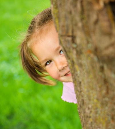 hide and seek: Cute little girl is playing hide and seek outdoors