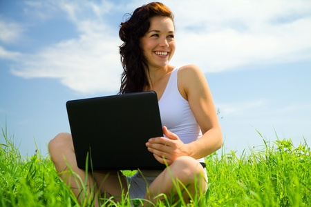 Cute cheerful girl is sitting on green grass with laptop photo