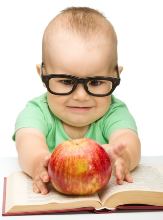 bite: Cute little child is playing with red apple while sitting at table, isolated over white