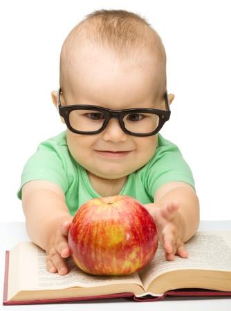 enfant fach�: Mignon petit enfant joue avec pomme rouge alors qu'il �tait assis � table, isol� sur blanc