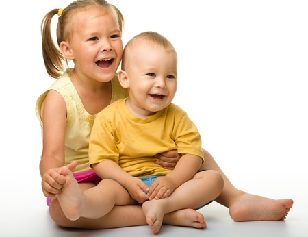 sister: Two children (a girl and a boy) are having fun while sitting on floor, isolated over white Stock Photo